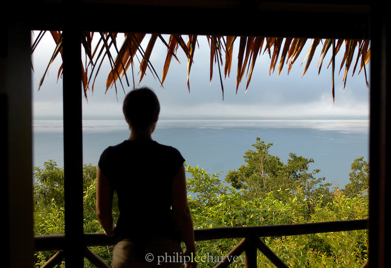 Woman on a balcony looking out over Lake Peten Itza at Tikal, Guatemala