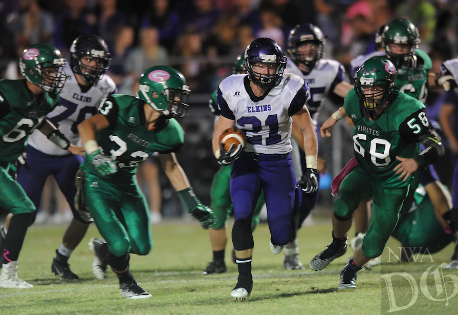 NWA Democrat-Gazette/ANDY SHUPE<br /> Colten Vaught (21) of Elkins carries the ball Friday, Oct. 28, 2016, ahead of Hunter Cartwright (33) and Trey Burnett (58) of Greenland during the first half of play at Jonathan Ramey Memorial Stadium in Greenland. Visit nwadg.com/photos to see more photographs from the game.