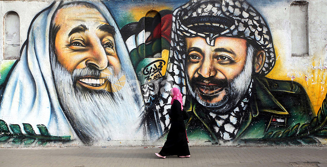 Palestinians passe by a mural depicting late Palestinian leader Yasser Arafat in Gaza City on Oct. 31, 2012. Palestinian authorities confirmed the November timetable to exhume the remains of former Palestinian leader Yasser Arafat by criminal investigators from France, and said a separate Swiss investigative team would arrive in the West Bank city of Ramallah at the same time to find out how the Palestinian leader died. Photo by Ashraf Amra