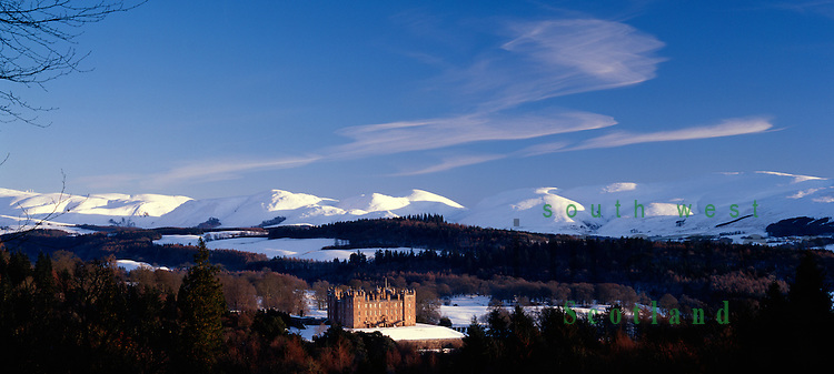 Scottish castle Drumlanrig Castle in a winter landscape with the snow covered Lowther Hills behind Nithsdale Dumfries and Galloway Scotland UK