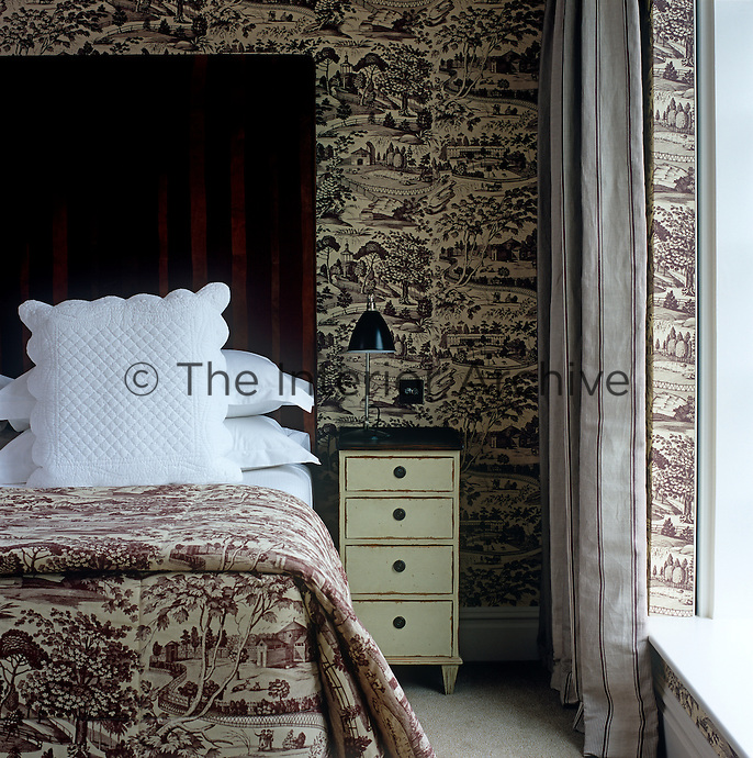 The matching toile de Jouy on the walls and bedding gives a sense of cohesion to this hotel bedroom whilst the striped curtains and headboard add a note of contrast