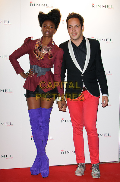 Shingai Shoniwa & Dan Smith of The Noisettes.The Rimmel London party, Battersea Power Station, London, England..September 15th, 2011.full length black shorts brown burgundy maroon jacket gold necklace grey gray belt suede purple thigh high over the knee otk boots hands on hips holding hands red jeans denim.CAP/CJ.©Chris Joseph/Capital Pictures.