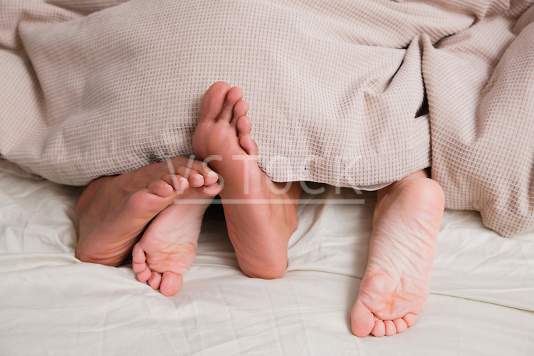 USA, New York City, feet of couple sleeping in bed