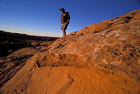 Man checking out the setting sun from slickrock dunes, Sandflats Campground, Moab, Utah
