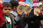 Palestinian children hold bread patties during a protest against aid cuts, outside the United Nations' offices in Khan Yunis in the southern Gaza Strip on January 28, 2018. On January 16, Washington held back $65 million that had been earmarked for the UN relief agency for Palestinian refugees, UNRWA. Photo by Ashraf Amra
