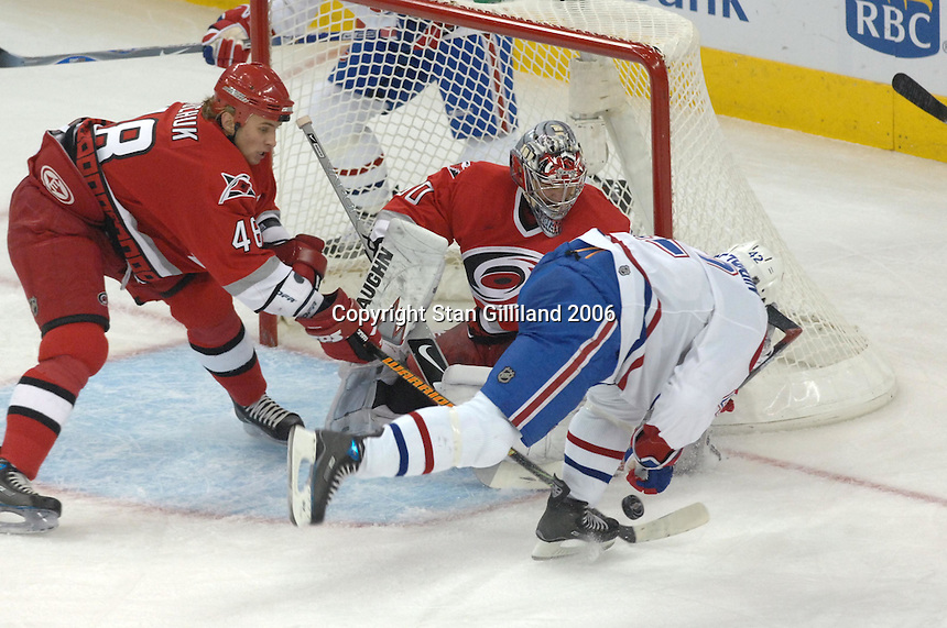 Montreal Canadiens Alexander Perezhogin loses control of the puck in the crease defended by the Carolina Hurricanes goalie Cam Ward and Anton Babchuk (48) during an NHL hockey game Thursday, Nov. 2, 2006 in Raleigh, NC.<br />