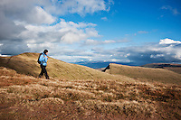 Female hiker hiking in mountains of Brecon Beacons national park with view of Pen Y Fan and Cribyn, Wales