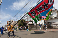 A large colourful flag is paraded in front of the mikoshi or portable shrines during the  Kanamara matsuri or festival of the Steel phallus Kawasaki Daishi, Kawasaki, Kanagawa, Japan. Sunday, April 2nd 2017. The Kanamara Penis festival takes place on the first Sunday of April and celebrates the local legend of a penis eating demon who was defeated after being tricked into biting a steel phallus. The festival is popular with Japan's gay community and now uses its notoriety to raise money for HIV and AIDS charities. It is also wildly popular with foreign and Japanese.tourists.