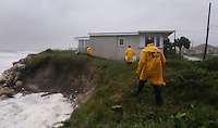 KELLY JORDAN/The Times-Union--082108--Members of the St.Johns County Fire and Rescue Department, from left Public Information Officer Jeremy Robshaw, Operations Chief Carl Shank and Special Operations Chief Joel Sneed try to be safe along a steep edge as they check out homes that are dangerously close to falling into the ocean as erosion takes valuable inches of sand away from their foundations in Vialno Beach as the St. Augustine area feels the effects of Tropical Storm Fay Thursday afternoon, August 21, 2008. This is part of their normal rounds as they report storm related damage back to the Emergency Operations Center.(The Florida Times-Union, Kelly Jordan)