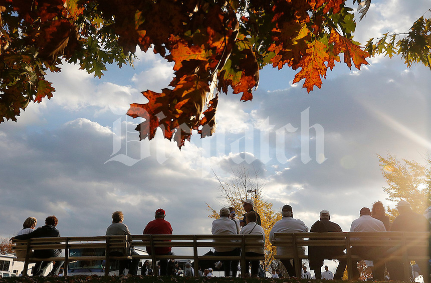 OSU and Penn State fans line up on a bench under fall leaves before the first quarter of their game at Beaver Stadium in State College, PA on October 25, 2014. (Columbus Dispatch photo by Brooke LaValley)