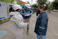 BOGOTA, COLOMBIA - MAY 12: A worker gives his health information to a woman before entering a construction site on May 12, 2020 in Bogota, Colombia. Colombian President Ivan Duque extended COVID-19 lockdown from May 11 to 25, including some exceptions by industry and territory. (Photo by VIEW press/Getty Images)