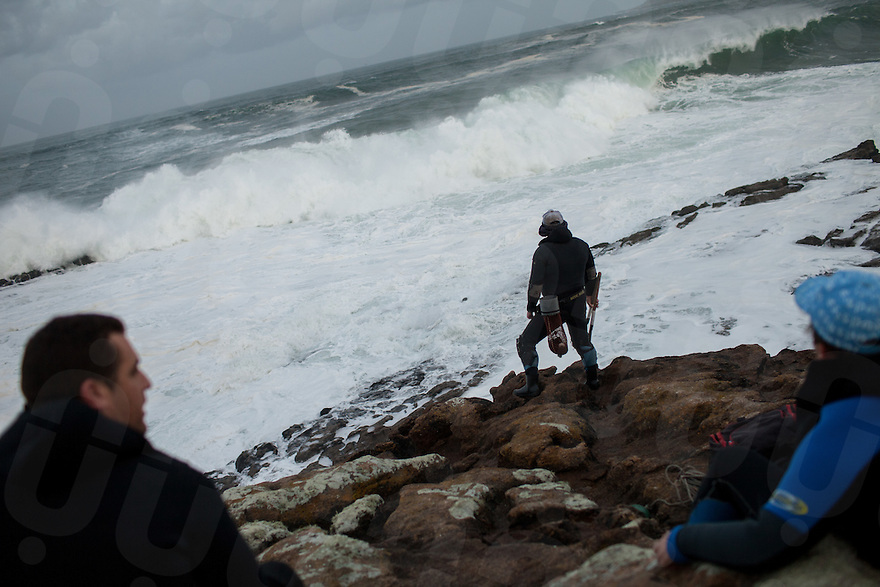 December 12, 2011 - Laxe (La Coruña). Julio looks at the giant waves crashing on the rocks where he's going to fish. Percebeiros have to watch carefully at the condition of the sea, a false step and they could fall into the ferocious current and die. © Thomas Cristofoletti 2011
