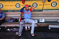 """OAKLAND, CA - AUGUST 26:  Robinson Chirinos #61 of the Texas Rangers gets ready in the dugout before the game against the Oakland Athletics at the Oakland Coliseum on Saturday, August 26, 2017 in Oakland, California. Note: both teams are wearing special colorful uniforms for """"Players Weekend"""" that also include nicknames on the backs of their jerseys. (Photo by Brad Mangin)"""
