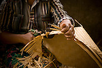 A woman cuts the brim of a hat in rural Lombok, Indonesia.