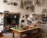 Room view of the kitchen showing the table with vegetables on it, the kitchen range alight and herbs hanging from the ceiling at Wordsworth House. A cook is working at the table.M.R.