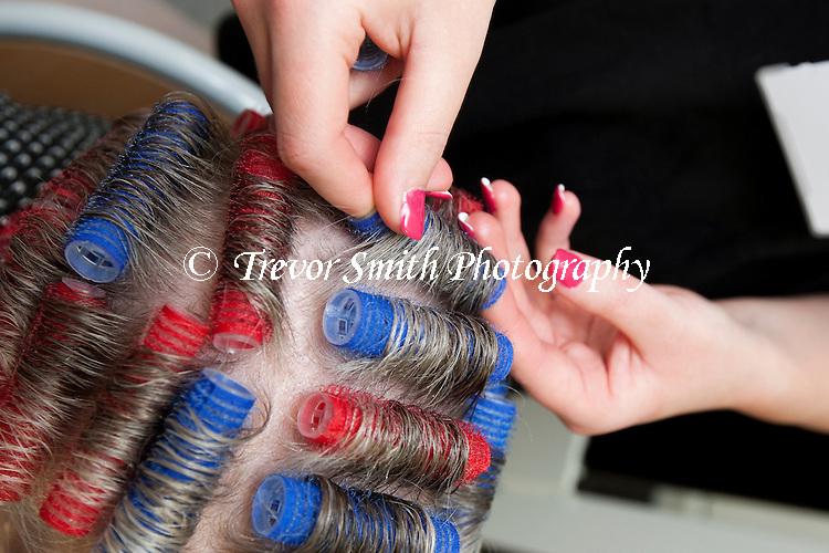 Hairdresser using plastic hair rollers in a senior womens hair