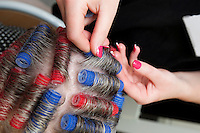 Hairdresser using plastic hair rollers in a senior womens hair