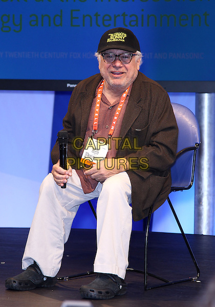 Danny Devito.Danny Devito makes an appearance at the Panasonic booth at the 2013 Consumer Electronics Show at the Las Vegas Convention Center, Las Vegas, NV., USA..January 9th, 2013.full length brown jacket baseball cap hat beige trousers chair sitting glasses.CAP/ADM/MJT.© MJT/AdMedia/Capital Pictures.
