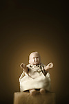 Vintage miniature baby doll in spotlight