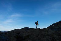 Female hiker stands on mountain ridge and looks into distance, Moskenesøy, Lofoten Islands, Norway