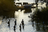 MADAGASCAR, village AMBOHITSARA at canal des Pangalanes, tribe ANTAMBAHOAKA, children on the way home from school / MADAGASKAR, Mananjary, Dorf AMBOHITSARA am canal des Pangalanes,  Volksgruppe ANTAMBAHOAKA, Schulweg durchs Wasser