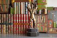 A detail in the kitchen of an early 20th century collection of biscuit tins disguised as books and a bronze sculpture
