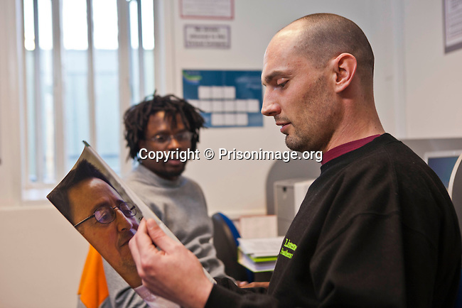 A prisoner looks through a Open University prospectus.  Open University working with prisoners in the education department at HMP Featherstone.