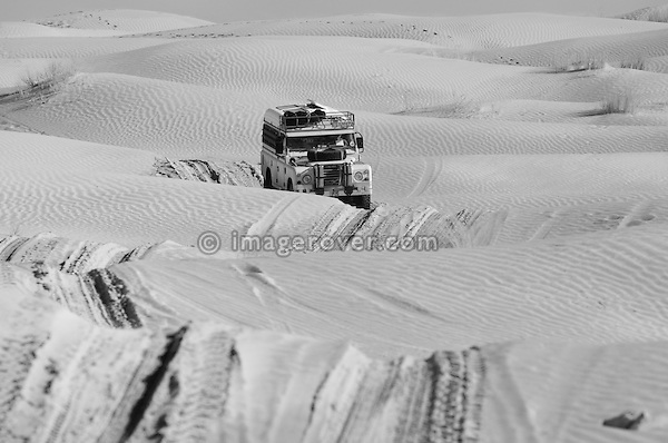 Africa, Tunisia, nr. Tembaine. Desert traveller Siegried driving his 1978 Land Rover Series 3 Dormobile through a sandfield with dunes close to Tembaine on the eastern edge of the Grand Erg Oriental. --- No releases available, but releases may not be needed for certain uses. Automotive trademarks are the property of the trademark holder, authorization may be needed for some uses.  --- Info: Image belongs to a series of photographs taken on a journey to southern Tunisia in North Africa in October 2010. The trip was undertaken by 10 people driving 5 historic Series Land Rover vehicles from the 1960's and 1970's. Most of the journey's time was spent in the Sahara desert, especially in the area around Douz, Tembaine, Ksar Ghilane on the eastern edge of the Grand Erg Oriental.