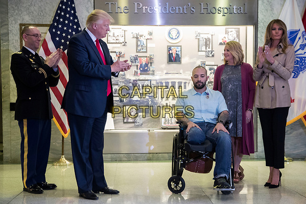 US President Donald J. Trump (2-L), with First Lady Melania Trump (R), applaud Sergeant First Class Alvaro Barrientos (C), with his wife Tammy Barrientos (2-R), after awarding him the Purple Heart during a visit to Walter Reed National Military Medical Center in Bethesda, Maryland, USA, 22 April 2017. Sergeant First Class Alvaro Barrientos was recently injured in Afghanistan while deployed and for the wounds he sustained, he is receiving the Purple Heart.<br /> CAP/MPI/RS<br /> &copy;RS/MPI/Capital Pictures