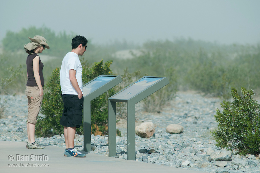Park visitors stop to read an interpretive sign at the Mesquite Flat Sand Dunes in Death Valley National Park, California
