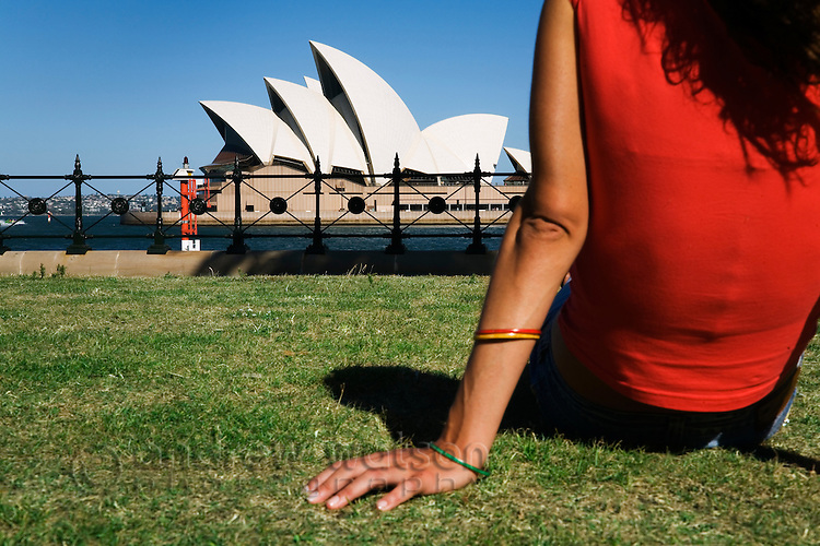 A woman relaxes at Dawes Point Reserve opposite the Sydney Opera House.  Sydney, New South Wales, AUSTRALIA.