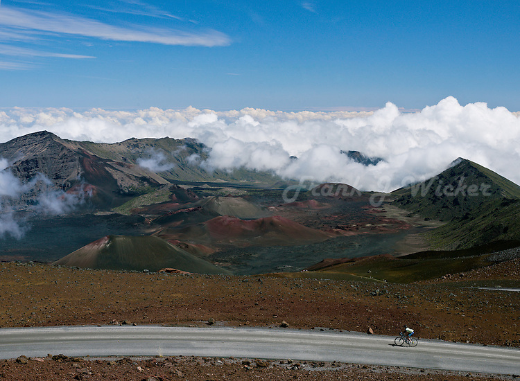 High above the clouds at the summit of HALEAKALA NATIONAL PARK on Maui in Hawaii a bike rider completes his personal challenge for endurance