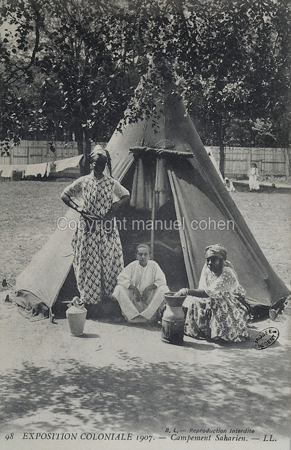 Saharan Camp, Africans with their tent displaying their way of life to visitors at the Colonial Exhibition of 1907, held in the Jardin d'Agronomie Tropicale, or Garden of Tropical Agronomy, in the Bois de Vincennes in the 12th arrondissement of Paris, postcard from the nearby Musee de Nogent sur Marne, France. The garden was first established in 1899 to conduct agronomical experiments on plants of French colonies. In 1907 it was the site of the Colonial Exhibition and many pavilions were built or relocated here. The garden has since become neglected and many structures overgrown, damaged or destroyed, with most of the tropical vegetation disappeared. The site is listed as a historic monument. Picture by Manuel Cohen / Musee de Nogent sur Marne