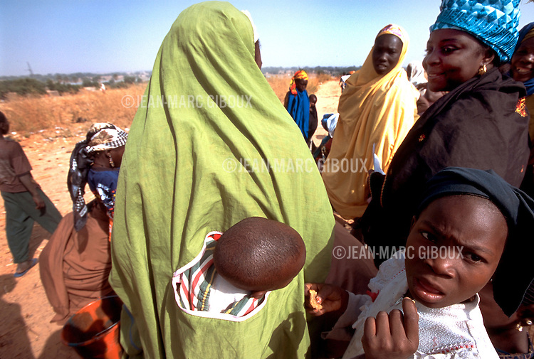 ©JEAN-MARC GIBOUX.DECEMBRE 5, 2003. MARADI, NIGER.A POLIO VACCINATION TEAM IMMUNIZE A CHILD WITH THE ORAL POLIO VACCINE IN A MARKET IN MARADI, DURING THE NATIONAL IMMUNIZATION DAYS (NIDs) IN NIGER. NIGER HAD 17 RECORDED CASES OF POLIO IN 2003 (SECOND WORST IN AFRICA BEHIND NIGERIA) . 11 OF THIS CASES WERE IN MARADI DISTRICT ALONE .