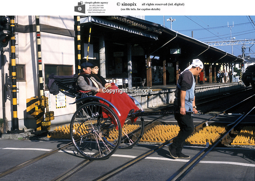 A couple on a rickshaw passing a railway station in Kamakura, Japan.