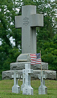 Flags fly at the gravestones of priests buried in the cemetery at St. Josephs Church in Somerset, Ohio. The church is the oldest Catholic church in Ohio...<br />