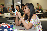 New York, NY, USA - June 24, 2012: Emily Kwan, from New Jersey, folds a complex Origami model of a swallow designed by Sipho Mabona at a class he is teaching during the OrigamiUSA 2012 convention held at Fashion Institute of Technology in New York City. This model is folded from one square sheet of paper.
