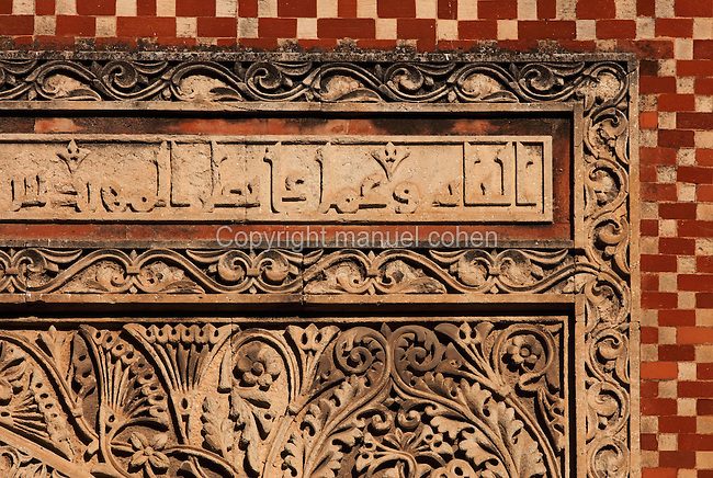 Architectural detail of the Puerta de San Ildefonso, built under Al-Hakam II in the 10th century, one of the West facade entrances to the Cathedral-Great Mosque of Cordoba, on the Calle Torrijos in Cordoba, Andalusia, Southern Spain. This detail shows the frame of the arch, with kufic inscription, mosaic work and intricately carved vegetal patterns. The first church built here by the Visigoths in the 7th century was split in half by the Moors, becoming half church, half mosque. In 784, the Great Mosque of Cordoba was begun in its place and developed over 200 years, but in 1236 it was converted into a catholic church, with a Renaissance cathedral nave built in the 16th century. The historic centre of Cordoba is listed as a UNESCO World Heritage Site. Picture by Manuel Cohen