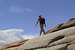 Man walking on slickrock sandstone in Arches National Park, Utah, USA. .  John offers private photo tours in Arches National Park and throughout Utah and Colorado. Year-round.