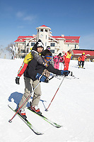 "A man skis downhill while carrying a child in the Club Med Sun Mountain Yabuli Resort, the Club Med's first holiday resort in China. The resort is jointly managed by Melco China Resorts (Holding) Limited & Club Med Asie S.A. (""Club Med"")."