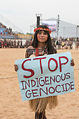 "A Pataxo woman protests against Brazilian government policies on indigenous issues carrying a sign which reads ""stop indigenus genocide"" during the International Indigenous Games, in the city of Palmas, Tocantins State, Brazil. Photo © Sue Cunningham, pictures@scphotographic.com 25th October 2015"