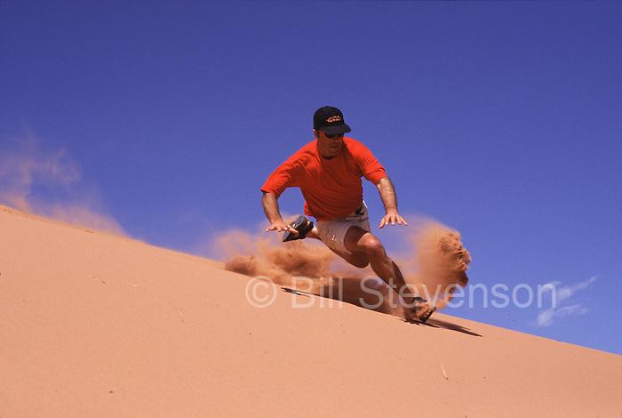 A photo of a man running down a sand dune near Moab, UT.
