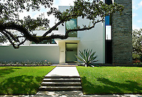 The exterior of a modern house in Texas bathed in bright sunshine