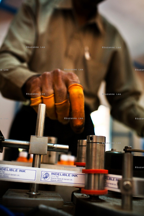 30th March 2009, Mysore, Karnataka, India:  A factory worker adjusts the labels as phials of ink get labeled by a machine. It is the first year that a machine is used as all this used to be done manually since 1962. .Indelible ink that will be used for the upcoming 2009 India Lok Sabha Elections are being labeled. Each phial contains 10ml of ink and if properly applied, can be used to mark as many as 700 voters. Only one company, Mysore Paints and Varnish, manufactures the secret formula of indelible ink that is used for all Indian elections since the biggest democratic nation in the world started using ink to mark the fingers of its voters in 1962.   Photo by Suzanne Lee/The National