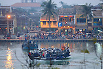 Asia, Vietnam, Hoi An. Hoi An old quarter nr. central market. Crossing the Thu Bon river by ferry overlooking lively Bach Dang St. The historic buildings, attractive tube houses, and decorated community halls have 1999 earned Hoi An's old quarter the status of a UNESCO World Heritage Site. To protect the old quarter's character stringent conversation laws prohibit alterations to buildings, as well as the presence of cars on the roads.