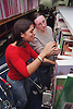 Teenage girl with physical disability looking through books in college library with friend,