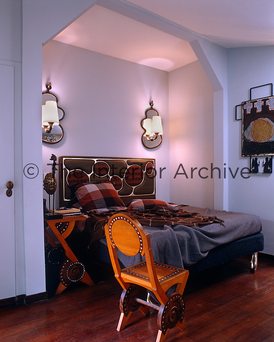 Flanked by a pair of sconces the double bed in the master bedroom has been tucked into a cosy alcove