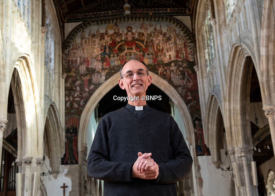 BNPS.co.uk (01202 558833)<br /> Pic: PhilYeomans/BNPS<br /> <br /> Delighted vicar Kelvin Inglis.<br /> <br /> Doom finally has its day! - A 500 year old 'Day of Judgement' painting, that has survived Henry VIII th, the Puritans and even Victorian prudery has been restored to its former glory.<br /> <br /> Thought to be the largest medieval 'Doom' painting in the country, the striking image been painstakingly restored after a tumultuous 500 year history on the chancel arch of St Thomas Becket church in Salisbury.<br /> <br /> Originally painted in the 15th century, the chancel was white-washed during the Reformation before being uncovered nearly 300 years later in the early 19th century. <br /> <br /> Prudish Victorian's shocked by the naked images then recovered it before it finally re-emerged in 1881 as opinions relaxed. <br /> <br /> Experts have spent three months conserving the faded painting, which included injecting lime slurry behind areas of paint to affix them again to the wall. and delicately 'touching up' in places before finishing it with varnish to bring out its colour.<br /> <br /> Most pre 16th century churches and cathedrals in Britain would have been plastered with religious images and iconography to encourage their often illiterate congregation to good behaviour.<br /> <br /> But during Henry VIII th Protestant Reformation churches were stripped of all graven imagery and the paintings were either whitewashed over or completely destroyed.<br /> <br /> Because of this very few works still survive today making the Salisbury fresco a truly remarkable survivor.<br /> <br /> The restoration is part of a larger set of works at the historic church which are due to cost £1.5million.