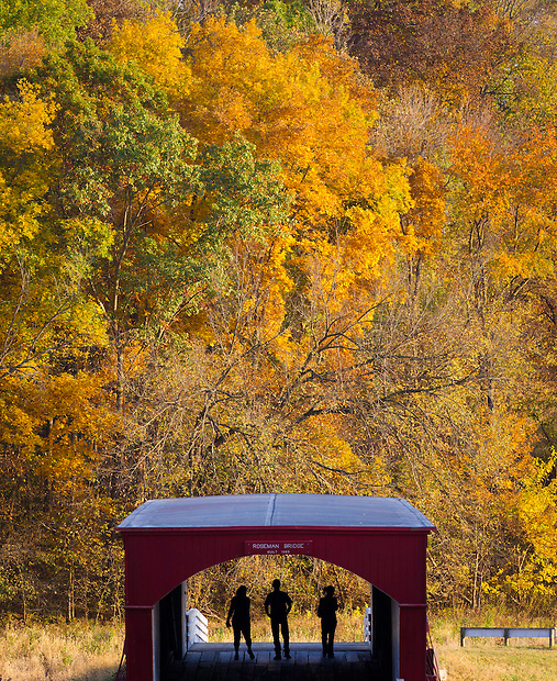 A trio of visitors stroll Roseman Bridge, one of Madison County's six remaining historic covered bridges as Fall colors bloom west of Winterset, Iowa on October 9.