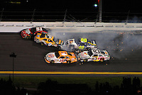 Jul. 2, 2011; Daytona Beach, FL, USA; NASCAR Sprint Cup Series drivers Tony Stewart (14) and Brian Vickers (83) go low to avoid the crashing cars of Landon Cassill (51), Marcos Ambrose (9) and David Reutimann (00) during the Coke Zero 400 at Daytona International Speedway. Mandatory Credit: Mark J. Rebilas-